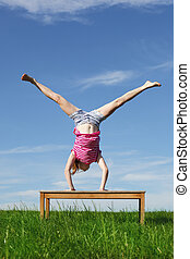 Handstand - Young girl doing a handstand in a meadow