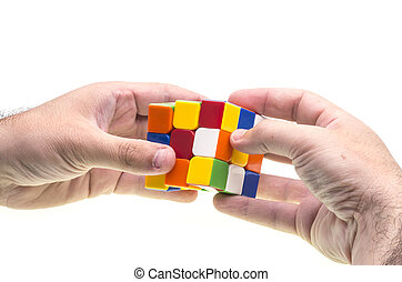 Resolving Rubiks cube - Hands resolving a Rubiks cube over...