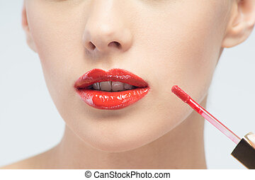 Beautiful woman applying lip gloss - Closeup portrait of...