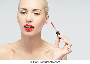 Beautiful woman applying lip gloss - Portrait of young...
