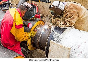 Welding team - Welders welding pipeline together, teamwork