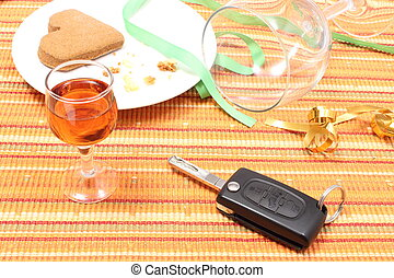 Car key with glass of wine on table after party - Closeup of...