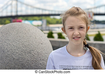 Girl posing next to a stone decorative sphere - Portrait of...