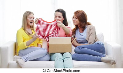 smiling teenage girls opening cardboard box -...