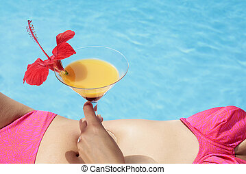 Summertime Cocktail - Woman in a bikini with a cocktail by a...