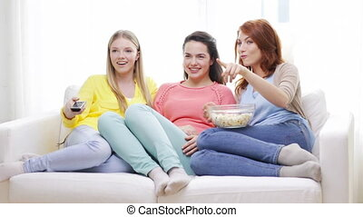 three smiling teenage girls watching tv at home - home,...