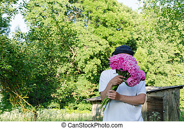 man hiding his face with peony bouquet garden - man hiding...