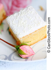 A fresh cake with a rose bud, close cup
