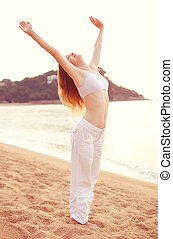 Young woman stretching on sea background