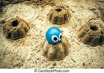 The Sandbox - A sandbox with sand cake and a rubber ball...