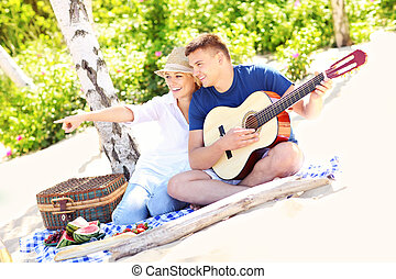 Happy couple on the beach with guitar