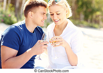 Romantic couple with champagne at the beach