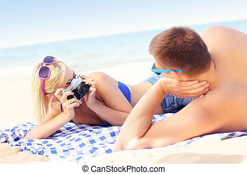 Woman taking a picture of her boyfriend at the beach