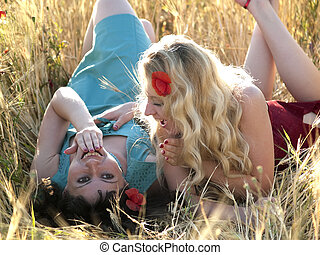SIsters in field - Two beautiful young ladies laying in...