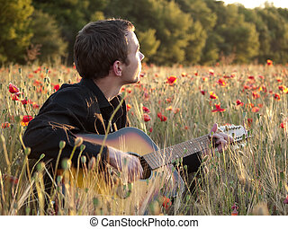Guitarist in field - Young man playing guitar in poppy field...