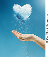 Heart shaped cloud rain storm - A hand holding a rain storm...