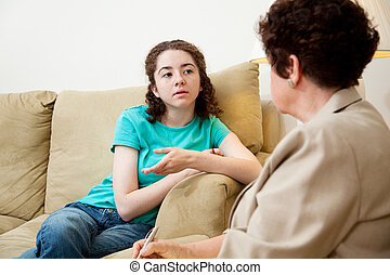 Teen Speaking with Counselor - Teen girl talking to a female...