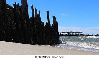 Old pier ruins on seashore - Old wooden pier ruins on sandy...