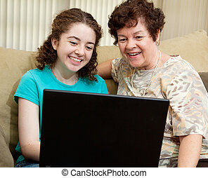 Teen and Mom with Laptop - Teen girl and her mother enjoy...