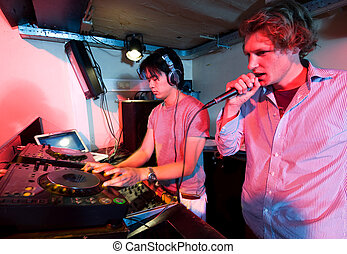 Dj in action - A DJ and a mc in action at a party in a...