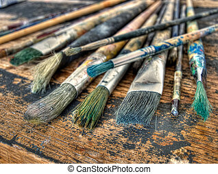 Painters brushes - Closeup of used brushes and colors in one...