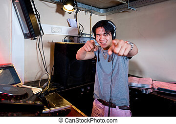 DJ in action - A Dj in a dj booth smiling and pointing at...