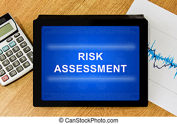 risk assessment word on digital tablet with calculator and...