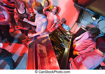 Nightclub - People dancing and flirting near the DJ booth at...