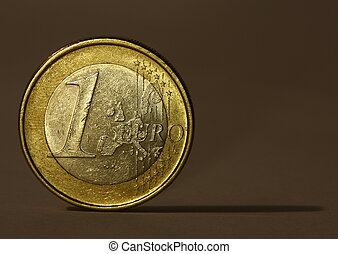 One Euro Coin - One Euro coin balancing on its edge, casting...
