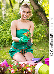 Young woman planting flowers - Smiling young woman planting...
