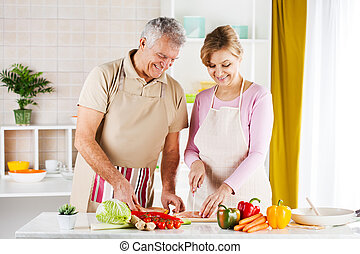 Preparing food - Happy Senior Couple cutting meat in the...