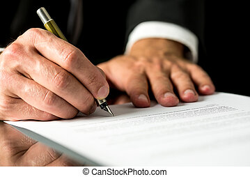 Man signing a typed document - Close up of the hands of a...