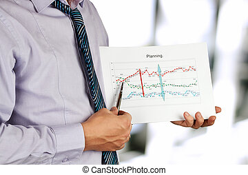 Businessman standing and showing graphics.