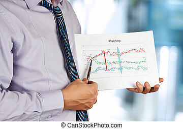 Businessman standing and showing graphic.