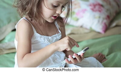 Little girl in white dress with mobile phone