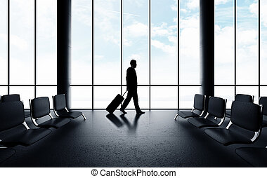 businessman walking in airport with luggage