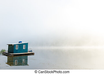 Lakehouse in fog - Floating lakehouse on calm foggy river at...