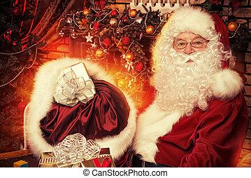 december - Santa Claus making Christmas gifts at home.
