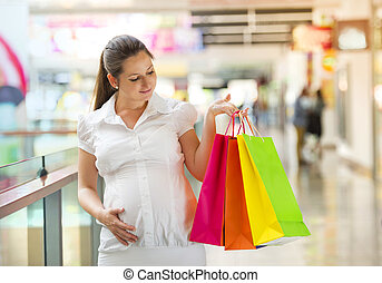 Pregnant woman shopping - Young pregnant woman with shopping...