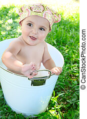 Baby Bath - Beautiful baby girl having a bath outdoors