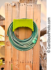 Hoses are rolled up in storage which in garden
