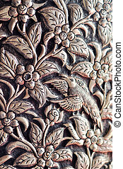 Silverware is carved by hand in a pattern of flowers and...