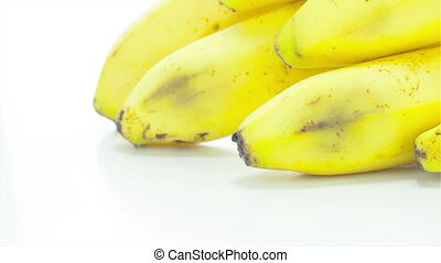 Raw banana rotating on the white table with white seamless...