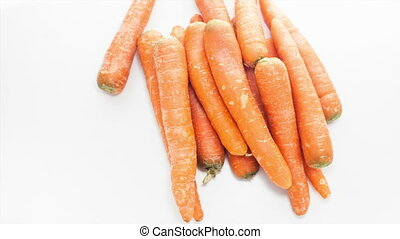 Raw carrots rotating on the white table with white seamless...