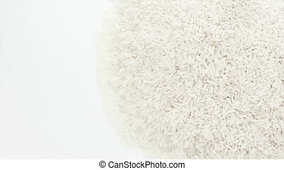 Raw rice rotating on the white table with white seamless...