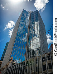 Blue sky and clouds reflecting on a building with mirrored...