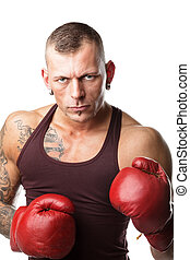 Boxer - muscular young man in boxing gloves, ready to fight