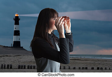 Girl with binoculars and lighthouse in twilight - Brunette...