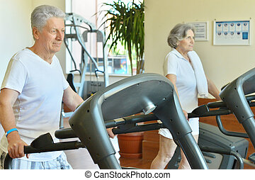 Couple in gym - Senior couple on running track in the gym