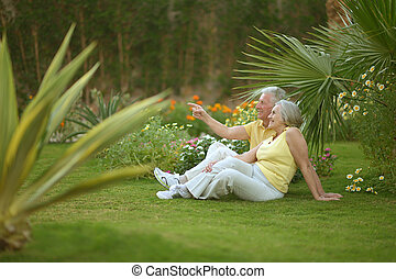 Senior couple sitting at tropic hotel garden on vacations